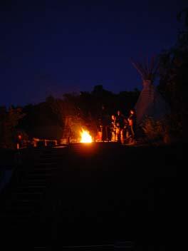 Das Lagerfeuer und das Tipi und die feiernden Menschen
